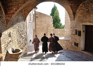 ASSISI, ITALY - july 22, 2017 . Monks walking along the street of ancient Assisi. The traditional italian medieval historic center in Umbria.