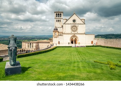 Assisi, Italy - May 22 2019: Classic view of famous Basilica of St. Francis of Assisi in beautiful spring day light with dramatic clouds in the sky Assisi, Umbria, Italy.