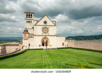 Assisi, Italy - May 22 2019: Classic view of famous Basilica of St. Francis of Assisi  in beautiful spring day light with dramatic clouds in the sky Assisi, Umbria, Italy