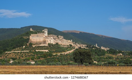 Assisi town on the hill with Basilica of San Francesco in front and medieval fortress Rocca Maggiore in the back on the clear summer day. Province of Perugia, Umbria region, Italy