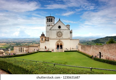 ASSISI, UMBRIA, ITALY - JUNE 30, 2018:the beautiful Basilica of St. Francis of Assisi located in the town of Assisi, Italy. Photo contains a Tuscan hillside view in the background