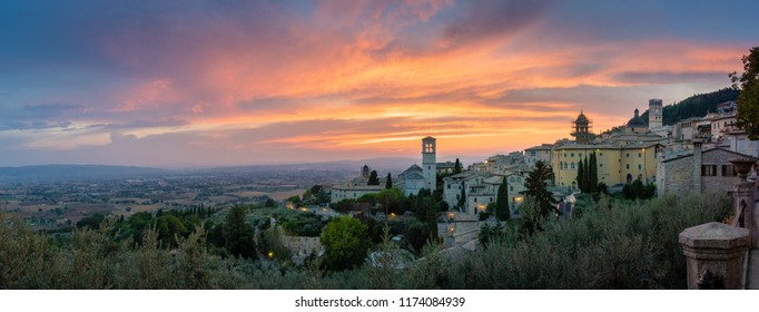 Assisi, Umbria Italy. Panoramic sunset in city of Assisi. Monumental, historic and romantic Italian countryside with roads, houses, churches. Skyline cityscape Assisi with hills of Umbria