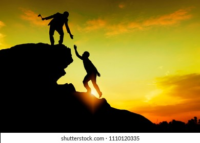Assistance, teamwork and achievement concept. silhouette of man helping friend climbing rock to top and success together