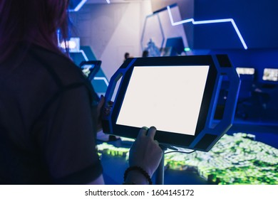 Assistant and a blank large display of a professional tablet on a computer game event or exhibition. Concept of digital assistance, type your text.