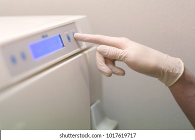 Assistant dentist chooses a program for processing a surgical instrument in an autoclave