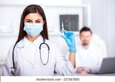Assistant doctor with a syringe. Against the background of the doctor sits at the table.