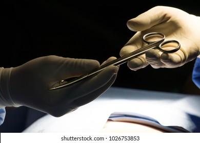 Assistant help professional doctor and sent scissor or forceps to him, hospital, health care and medical concept