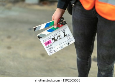 Assistant is holding a film flap in her hand.