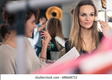Assistant improving young pretty model's make up before session