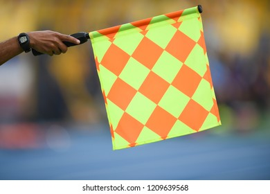Assistant referee hold flag , offside signal