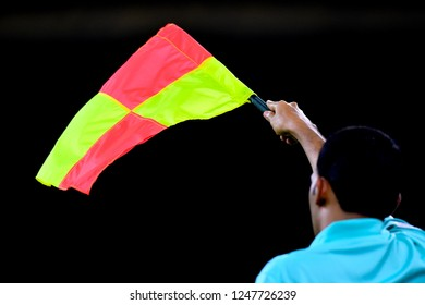 An assistant referee show offside flag.