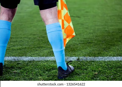 Assistant Referee Signals with flag in the soccer field