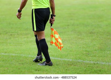 Assistant referees signalling with the flag on the sideline during a soccer match