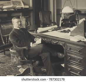Assistant Secretary of the Navy, Theodore Roosevelt at his desk, 1897-98. On the floor are discarded documents, appear in other office portraits of TR