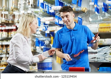 Assistant seller help buyer by demonstrating putty knife for filling at hardware store