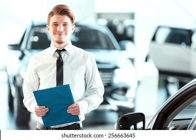 Assistant in vehicle search. Portrait of a handsome young car sales man in formalwear holding a clipboard and looking at camera in a car dealership