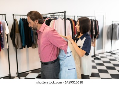 Assisting during fitting. Kind good-looking attractive lovely showroom consultant assisting a dark-haired bearded handsome customer during trying on a blazer.