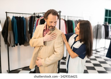 Assisting with fitting. Beautiful radiant alluring stylist helping a good-looking bearded dark-haired adult attractive male while trying on a new blazer.