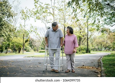 assisting her senior patient who's using a walker for support
