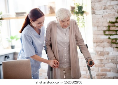 Assisting woman. Helpful caregiver smiling while assisting woman with crutches