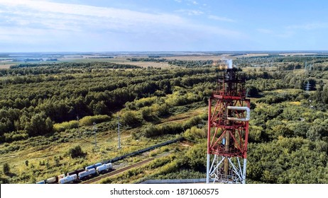 Associated gas flaring tower. Fiery torch. Aerial view.