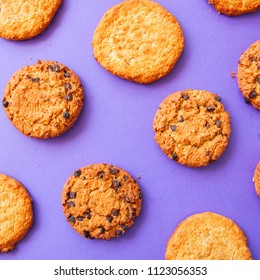 Assorted American traditional old fashioned cookies. Oatmeal and chocolate chips cookies on a purple background. Top view and square image.