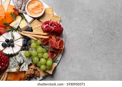 Assorted appetizers served on light grey table, top view. Space for text