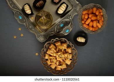 Assorted Arabian sweets and date chocolates in an antique tray along with Ramadan light. An Islamic festive food and background. View from above.