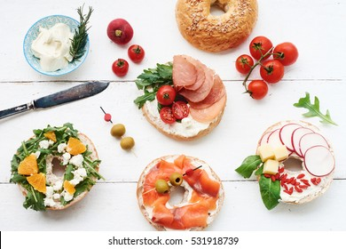 Assorted bagels with cream cheese, italian ham, cherry tomatoes, rocket salad, radish, cheddar, salmon and olives over white background. Copy space.