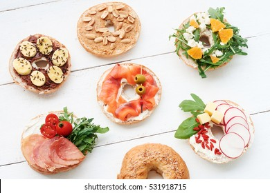 Assorted bagels with cream cheese, rocket salad, cherry tomatoes, salmon, olives, feta, tangerine, radish, cheddar, peanut butter and chocolate spread with bananas. White table, top view.