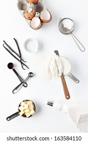 Assorted baking ingredients and tools: eggshells, vanilla pods, flour in measuring cup, spatula, measuring spoon with vanilla extract, butter, sea salt, piping bag and vintage sifter with icing sugar.