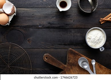 Assorted baking ingredients and tools on dark vintage wooden background: eggs, vanilla extract, flour in measuring cup, cinnamon, measuring spoons, cookie cutter, vintage cutting board, cooling rack.