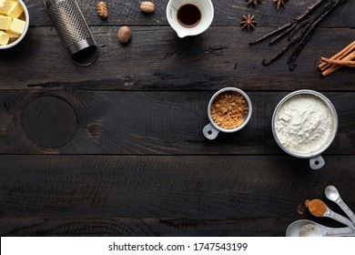 Assorted baking ingredients and tools on dark vintage wooden background: butter, nutmeg, vanilla extract, vanilla beans, flour in measuring cup, cinnamon, brown sugar, measuring spoons.