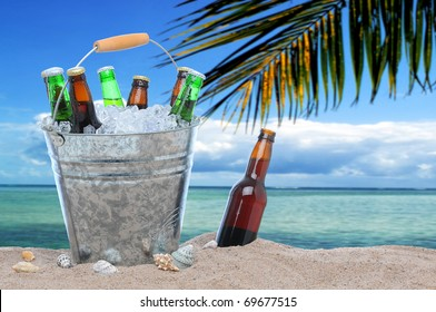 Assorted beer bottles in a bucket of ice and one in the sand on a tropical beach.