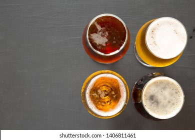 Assorted beers on a black surface, top view. Overhead, from above. Copy space.