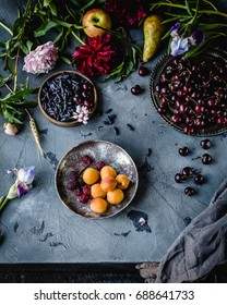 assorted berries, apricots and flowers in plates on a grey background with grey textile, top view