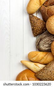 assorted of bread on white wooden background.