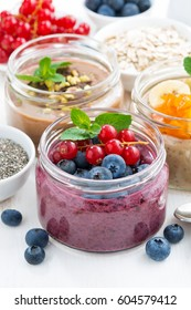 assorted breakfast of chia seeds and fruits in jars on white wooden table, vertical, closeup