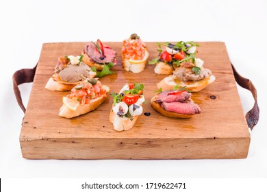 Assorted bruschett on a wooden board on a white background