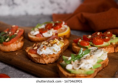 assorted bruschetta on a wooden board with avocado, egg, red fish and nuts