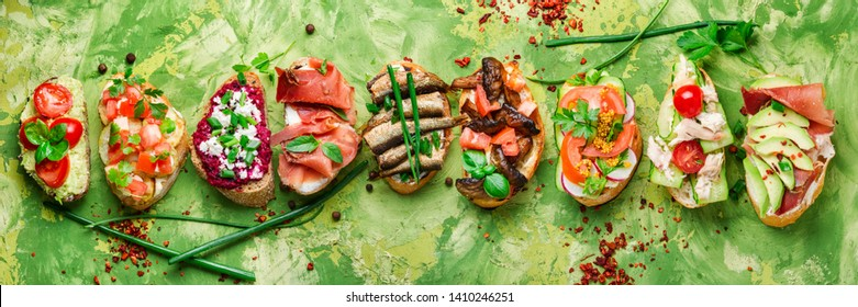 Assorted bruschetta with various toppings.Appetizing bruschetta.Variety of small sandwiches.Mix bruschetta