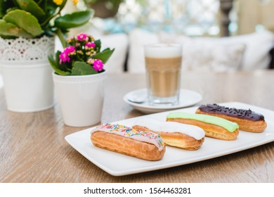 Assorted cakes Eclair with coffee on a wooden table