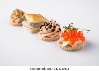 Assorted Canapes with Caviar and Pate. Beautifully decorated catering banquet menu. Food snacks and appetizers for buffet. Isolated on white background