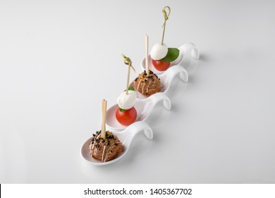 Assorted canapes on caprese skewers with cherry, mozzarella and basil and meatballs. Beautifully decorated catering banquet menu. Food snacks and appetizers for buffet. Isolated on white background