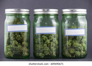 Assorted cannabis bud strains and glass jars over grey background - medical marijuana dispensary concept