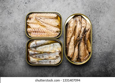 Assorted canned fish in a tin over gray concrete background: sardine, smoked sardine, mackerel. Tinned fish as a convenient, fast, healthy food and source of omega-3 fatty acids, protein and vitamin D