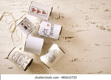 Assorted cans with married labels with copy space over scratched paint white background