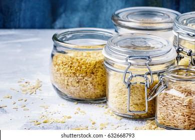 Assorted cereals in glass jars: kinoa, bulgur, couscous, orzo, brown rice, selective focus
