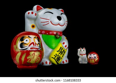 Assorted charms, talismans or lucky figures from Japan, including a large daruma, a small daruma, a large makeni-neko and a small maneki-neko.