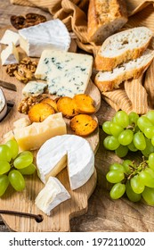 Assorted Cheese Brie, Camembert, Roquefort, parmesan, blue cream cheese with grape, fig, bread and nuts. wooden background. Top view